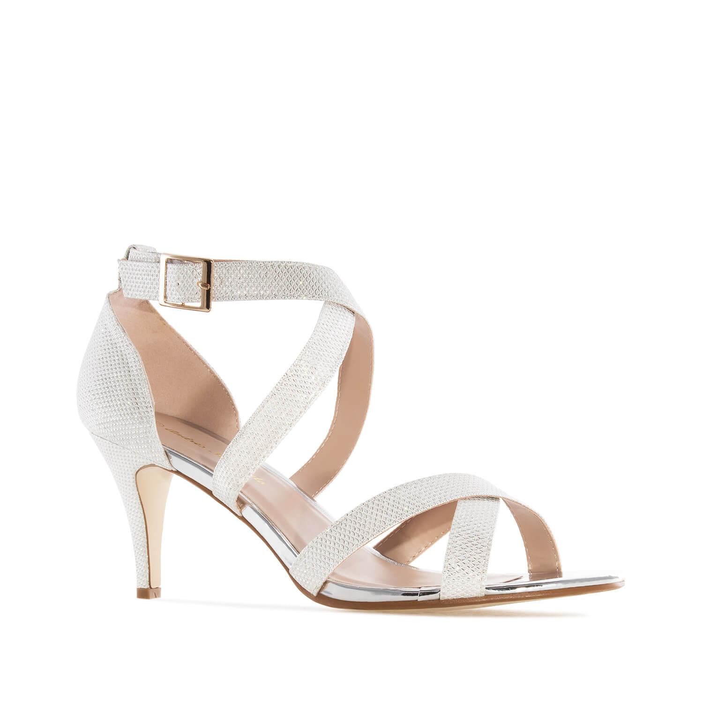 Hohtavat hopeat sandaalit.